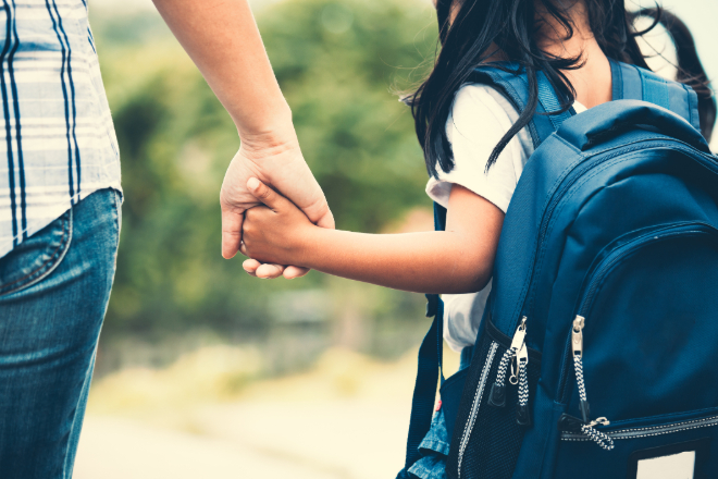 Mother daughter on way to school with backpack